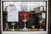Pub window with nationalist pride, football and snooker trophies Barnsley, South Yorkshire. Sunday Carvery, The Dove Inn - Connor Matheson - 2010s,2016,cities,City,EBF,Economic,Economy,food,FOODS,football,LICENSED,PHYSICAL,pride,pub,Public House,PUBLIC HOUSES,PUBS,SPO,Sport,sports,Sunday,Urban,Weekend,Window,Windows