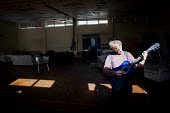 Young man playing guitar inside a disused school. Under a guardian scheme people are allowed to live there for a small rent as long as they take care of the building. St Margaret Of Antioch C Of E Pri... - connor matheson - 25-09-2016