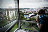 Council housing tenants and their friends watching a band performing at the Tramlines Music festival main stage from the window of a tower block flat. They do this to avoid paying for expensive ticket... - Connor Matheson - 2010s,2016,attention,attentive,audience,AUDIENCES,band,bands,blocks,can,cans,cities,City,cityscape,cityscapes,concert,concerts,Council,Council Housing,Council Services,Council Housing,Council Services