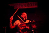Punk drummer under a sign that says Till We D.I.Y at tempory venue, The Lughole. Sheffield city center, South Yorkshire - Connor Matheson - 16-08-2016