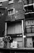 Docks at Clink Wharf on the River Thames, Southwark, London 1965 - Patrick Eagar - 1960s,1965,bays,cities,City,Clink Wharf,dock,DOCK WORKER,DOCK WORKERS,docker,dockers,dockland,docklands,docks,dockside,dockworker,dockworkers,employee,employees,Employment,export,exports,goods,harbor,