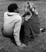 Black and white. Mixed race couple holding hands in a London park 1963 - Malcolm Aird - 10-05-1963
