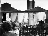 Young girl in her mothers arms outside by washing line in poor part of Manchester 1963 - Romano Cagnoni - 1960s,1963,adult,adults,back yard,child,CHILDHOOD,children,cities,City,clothes,daughter,DAUGHTERS,drying,drying clothes,EARLY YEARS,excluded,exclusion,FACTORIES,factory,FAMILY,female,females,garden,ga