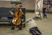 Berlin, Germany. Busker playing the cello in a Berlin subway - David Bacon - 2010s,2016,adult,adults,Berlin,busker,cello,cities,city,classical,COMMUTE,commuter,commuters,commuting,EBF,Economic,Economy,eu,Europe,european,europeans,eurozone,from work,german,germans,Informal Econ