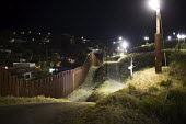 Nogales, Arizona, USA and Mexican border fence lit up at night by the U.S. Border Patrol. Mexico is on the left side of the fence - Jim West - 2010s,2016,America,american,americans,Arizona,border,border control,border controls,border fence,borders,CLJ,dark,divide,division,fence,foreign,foreigner,foreigners,Hispanic,Hispanics,immigrant,immigr