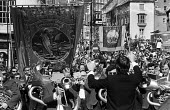 Durham Miners Gala, 1975. Annual procession of The Big Meeting through the City of Durham by miners from the pit villages of the north eastern area. Brass band from Monkwearmouth pit village playing o... - John Sturrock - 1970s,1975,ACE,band,bands,banner,banners,baton,Big Meeting,brass,brass band,cities,City,communities,community,conducting,conductor,conductors,County Durham,Culture,Durham Gala,Durham Miners Gala,Gala,