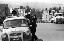 Edward Brown Conservative MP for Bath canvassing in his local constituency 1965, Vote Conservative - Romano Cagnoni - 1960s,1965,AUTO,AUTOMOBILE,AUTOMOBILES,AUTOMOTIVE,by election,campaign,campaigning,CAMPAIGNS,CANVASING,canvassing,car,cars,CONSERVATIVE,Conservative Party,conservatives,DEMOCRACY,Edward Brown,election
