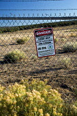 Mariano Lake, New Mexico, USA, Poisoned water for the Navajo. Sign warning of radiation danger on the site of an abandoned uranium mine, one of more than 500 abandoned mines on Navajo Nation land. Thi... - Jim West - 2010s,2016,abandoned,America,Amerindian,Amerindians,BAME,BAMEs,bilingual,BME,bmes,capitalism,capitalist,Chevron,communicating,communication,communities,community,contaminated,contamination,country,cou