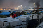 Refugees in the makeshift Jungle camp at dusk, prior to a demolition planned by French authorities. Calais, France. - Jess Hurd - 23-10-2016