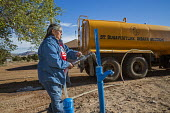 Thoreau, New Mexico, clean water being delivered by St. Bonaventure Indian Mission for a Navajo family. A third of the Navajo Nation lack a water supply in some places because past uranium mining has... - Jim West - 2010s,2016,3rd,America,American,americans,Amerindian,Amerindians,arid,BAME,BAMEs,Belief,BME,bmes,charitable,charity,christian,christianity,christians,cistern,clean,clean water,communities,community,co
