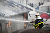 Firefighter spraying fires during the eviction of refugees from the Jungle camp, Calais, France - Jess Hurd - France,2010s,2016,adult,adults,authorities,BAME,BAMEs,Black,BME,bmes,burn,burning,BURNS,Calais,camp,camps,DEMOLISH,DEMOLISHED,demolition,DEVELOPMENT,Diaspora,displaced,diversity,employee,employees,Emp