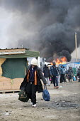 Fires rage during the eviction of refugees in the Jungle camp, Calais, France. - Jess Hurd - France,2010s,2016,adolescence,adolescent,adolescents,African,Africans,authorities,bag,bags,BAME,BAMEs,Black,BME,bmes,boy,boys,burn,burning,BURNS,Calais,camp,camps,child,children,DEMOLISH,DEMOLISHED,de