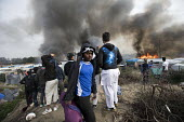 Fires rage during the eviction of refugees in the Jungle camp, Calais, France. - Jess Hurd - France,2010s,2016,adolescence,adolescent,adolescents,Afghan,Afghans,African,Africans,authorities,BAME,BAMEs,Black,BME,bmes,boy,boys,burn,burning,BURNS,Calais,camp,camps,child,children,DEMOLISH,DEMOLIS