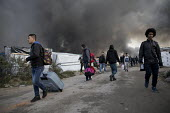 Refugees hastily leaving the camp as fires rage during the eviction of refugees from the Jungle, Calais, France. - Jess Hurd - France,2010s,2016,Afghan,Afghans,African,Africans,authorities,bag,bags,BAME,BAMEs,Black,BME,bmes,burn,burning,BURNS,Calais,camp,camps,DEMOLISH,DEMOLISHED,demolition,DEVELOPMENT,Diaspora,displaced,dive