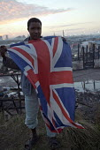 Young refugee with Union Jack flag poses in front of the burnt out remains of the Calais Jungle refugee camp after fires rage during eviction by French authorities, France. - Jess Hurd - France,2010s,2016,adolescence,adolescent,adolescents,African,Africans,authorities,BAME,BAMEs,Black,BME,bmes,burnt,burnt out,Calais,camp,camps,charred,DEMOLISH,DEMOLISHED,demolition,DEVELOPMENT,Diaspor