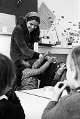 White Lion Free School Islington 1973. A radical experiment in local community schooling funded by donations with no timetable, no curriculum and no rules for the pupils. Teacher with younger children... - Angela Phillips - 1970s,1973,alternative,anarchic,BAME,BAMEs,BEMM,BEMMs,black,BME,bmes,child,CHILDHOOD,children,cities,city,class,communicating,communication,communities,community,diversity,donations,EDU,educate,educat