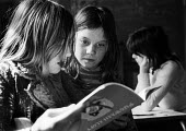 White Lion Free School Islington 1973. A radical experiment in local community schooling funded by donations with no timetable, no curriculum and no rules for the pupils. Two girls reading together. - Angela Phillips - 1970s,1973,alternative,anarchic,book,books,child,child children,CHILDHOOD,children,cities,city,class,communities,community,donations,EDU,educate,educating,Education,educational,experiment,female,femal