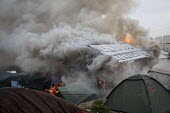 Volunteer firefighters try and save tents as fires rage during the eviction of refugees from the Jungle camp, Calais, France - Jess Hurd - 2010s,2016,adult,adults,authorities,BAME,BAMEs,Black,BME,bmes,burn,burning,BURNS,Calais,camp,camps,DEMOLISH,DEMOLISHED,demolition,DEVELOPMENT,Diaspora,displaced,diversity,ethnic,ethnicity,eu,Europe,eu