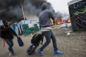 Refugees hastily leave the camp as fires rage during the eviction of refugees in the Jungle, Calais, France. - Jess Hurd - France,2010s,2016,African,Africans,authorities,bag,bags,BAME,BAMEs,Black,BME,bmes,burn,burning,BURNS,Calais,camp,camps,DEMOLISH,DEMOLISHED,demolition,DEVELOPMENT,Diaspora,displaced,diversity,Eritrean,