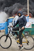 Young refugee on his bike as fires rage during the eviction of refugees in the Jungle camp, Calais, France. - Jess Hurd - 26-10-2016