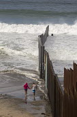 Tijuana, Mexico - The U.S.-Mexico border fence where it meets the Pacific Ocean. - Jim West - 2010s,2016,adult,adults,american,americans,americas,barrier,beach,BEACHES,border,border control,border controls,border fence,border wall,borders,COAST,country,countryside,couple,COUPLES,Diaspora,divid