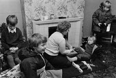 Sylvia Thirlwell at home helping her children get ready for school. Stonehaugh, Kielder Forest, Northumberland 1985 - Denis Doran - 1980s,1985,adult,adults,boy,boys,child,CHILDHOOD,children,cold,domestic,employee,employees,Employment,FEMALE,Forest,frozen,getting dressed,helping,home,homes,house,houses,Housing,job,jobs,juvenile,juv