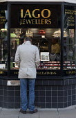 Shopper looking at jewellery in a shop window, Jago Jewellers, Stratford upon Avon, Warwickshire - John Harris - 2010s,2016,bought,buy,buyer,buyers,buying,choice,choosing,commodities,commodity,consumer,consumers,customer,customers,deciding,decisions,EBF,Economic,Economy,gold,goods,jeweller,jewellers,jewellery,je