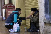 Homeless woman on the streets, Coventry Precinct. A passer by giving food, kindness and concern - John Harris - 2010s,2016,age,ageing population,Asian,Asians,assisting,attention,attentive,BAME,BAMEs,black,BME,bmes,charitable,charity,cities,City,City centre,comforting,communicating,communication,concern,conversa