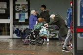 Elderly woman pushing a disabled woman in a wheelchair. Shoppers, Coventry Precinct - John Harris - 12-11-2016