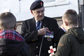 Old soldier explaining his medals to two boys. Remembrance Sunday, Shirebrook, Derbyshire - John Harris - 2010s,2016,2nd,ACE,age,ageing population,armed forces,army,boy,boys,child,CHILDHOOD,children,Culture,dead,death,DEATHS,died,elderly,explain,explaining,juvenile,juveniles,kid,kids,male,man,medal,medals