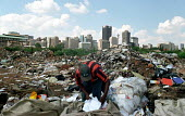 Man picking over a rubbish dump, Johannesburg, South Africa, with city office blocks in the background - Chris Smith - 2000s,2002,africa,African,Africans,blocks,cities,city,cityscape,cityscapes,collecting,collection,developing world,dump,eni,environment,Environmental degradation,Environmental Issues,excluded,exclusion