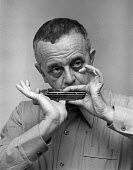 Larry Adler playing the harmonica, London 1972 - Martin Mayer - 1970s,1972,ACE,age,ageing population,Arts,cities,city,Culture,elderly,harmonica,interview,INTERVIEWED,INTERVIEWER,INTERVIEWING,interviews,jazz,Larry Adler,London,male,man,melody,men,mouth organ,music,