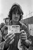 Fan holds up a ticket for The Who concert 1976 Charlton football ground, South East London - Martin Mayer - 1970s,1976,adolescence,adolescent,adolescents,audience,AUDIENCES,Charlton,Charlton football ground,cities,City,concert,concert ticket,concerts,fan,fans,football,London,male,man,melody,men,music,MUSICA