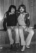 Alex Harvey (L) of The Sensational Alex Harvey Band 1976 with his drummer Ted McKenna, backstage at The Who concert, Charlton football ground, South East London - Martin Mayer - 1970s,1976,Alex Harvey,backstage,Band,bands,Charlton football ground,concert,concerts,drummer,football,friend,friends,friendship,friendships,London,male,man,melody,men,music,MUSICAL,musician,musicians