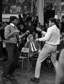 Muhammad Ali 1974 sparring with a pupil at Tulse Hill School, Brixton, London - Peter Arkell - 1970s,1974,African American,African Americans,BAME,BAMEs,black,Black and White,BME,bmes,boxer,boxers,boxing ring,Brixton,child,CHILDHOOD,children,cities,city,Comprehensive School,diversity,EDU,educate