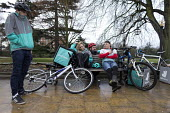 Deliveroo workers waiting for work, Leamington Spa, Warwickshire - John Harris - 2010s,2016,app,application,applications,apps,backpack,bench,bicycle,bicycles,BICYCLING,Bicyclist,Bicyclists,BIKE,BIKES,by hand,carries,carry,carrying,CELLULAR,collecting,communicating,communication,co