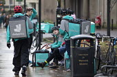 Deliveroo workers waiting for work, Leamington Spa, Warwickshire - John Harris - 2010s,2016,backpack,bench,bicycle,bicycles,BICYCLING,Bicyclist,Bicyclists,BIKE,BIKES,by hand,carries,carry,carrying,collecting,communicating,communication,contracts,conversation,conversations,Courier,