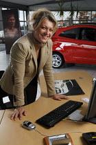 Woman sales person, showroom, Ford dealership, Herouville Saint Clair, France - Benoit Decout - 24-11-2010