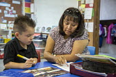Thoreau, New Mexico - Classroom assistant Jennifer Vandever works with a student in a kindergarten classroom at St. Bonaventure Indian School, a Catholic school on the Navajo Nation. - Jim West - 12-10-2016