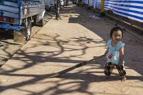 Child in the Street, Luang Prabang, Laos - David Bacon - 2010s,2015,Asia,asian,asians,buddha,Buddhism,buddhist,buddhists,child,CHILDHOOD,children,EMOTION,EMOTIONAL,EMOTIONS,female,females,girl,girls,happiness,happy,juvenile,juveniles,kid,kids,Lao,Laos,Laoti