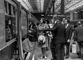 Upper class wedding guests boarding a train on their way to the wedding of Lady Fitzalan Howard, Victoria station, London 1975 - NLA - 1970s,1975,AFFLUENCE,AFFLUENT,boarding,Bourgeoisie,british,carriage,carriages,cities,city,elite,elitism,FEMALE,guests,high,high income,income,INEQUALITY,journey,JOURNEYS,Lady Fitzalan Howard,Leisure,L