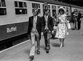 Upper class boys in their morning suits on their way to the wedding of Lady Fitzalan Howard, Victoria station, London 1975 - NLA - 1970s,1975,AFFLUENCE,AFFLUENT,boarding,Bourgeoisie,BOY,boys,british,buffet car,carriage,carriages,cities,city,elite,elitism,FEMALE,high,high income,income,INEQUALITY,journey,JOURNEYS,Lady Fitzalan How