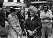 Upper class women in hats prior to boarding a train to the wedding of Lady Fitzalan Howard, Victoria station, London 1975 - NLA - 1970s,1975,AFFLUENCE,AFFLUENT,age,ageing population,boarding,Bourgeoisie,british,cities,city,communicating,communication,conversation,conversations,dialogue,discourse,discuss,discusses,discussing,disc