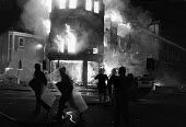 Brixton riots London 1985. Firefighters, burning building and riot police - NLA - 28-09-1985
