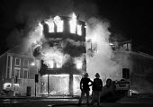 Brixton riots London 1985. Firefighters, burning building and overturned car - NLA - 28-09-1985
