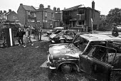 Day after the riots at Broadwater Farm housing estate, Tottenham, North London 1985. Burnt out cars - Peter Arkell - 1980s,1985,AUTO,AUTOMOBILE,AUTOMOBILES,AUTOMOTIVE,barricade,BARRICADES,Broadwater Farm,building,buildings,Burnt,burnt out,car,cars,cities,City,Farm,fire,fires,housing,inner city,London,rebellion,revol