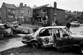 Day after the riots at Broadwater Farm housing estate, Tottenham, North London 1985. Burnt out cars - Peter Arkell - 1980s,1985,AUTO,AUTOMOBILE,AUTOMOBILES,AUTOMOTIVE,barricade,BARRICADES,Broadwater Farm,building,buildings,Burnt,burnt out,car,cars,cities,City,Farm,fire,fires,housing,inner city,London,overturned,rebe