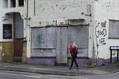 Student walking past a closed pub with Good Life graffeti, Hanley, Stoke on Trent, Staffordshire - John Harris - 2010s,2017,boarded up,building,buildings,cities,City,closed,closing,closure,closures,derelict,DERELICTION,disused,DOWNTURN,FEMALE,Graffiti,LICENSED,pedestrian,pedestrians,people,person,persons,propert