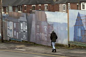 Woman walking past picture boards in front of house demolition, Hanley, Stoke on Trent, Staffordshire - John Harris - 2010s,2017,boards,building,buildings,cities,City,developer,developers,development,EBF,Economic,Economy,excluded,exclusion,FEMALE,HARDSHIP,house,houses,Housing,Housing Estate,impoverished,impoverishmen