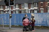 Woman with pushchair walking past picture boards in front of house demolition, Hanley, Stoke on Trent, Staffordshire - John Harris - 2010s,2017,adult,adults,boards,building,buildings,child,CHILDHOOD,children,cities,City,cross,Crossing The Road,developer,developers,development,EBF,Economic,Economy,families,family,FEMALE,highway,hous